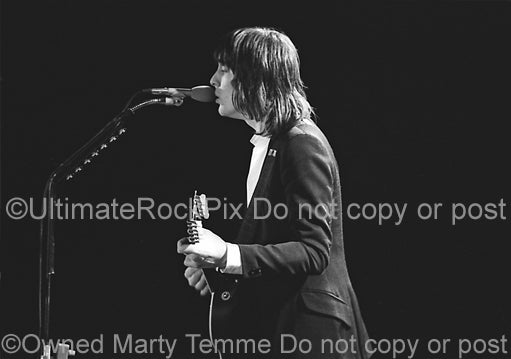 Photo of Todd Rundgren playing acoustic guitar in concert in 1981 by Marty Temme