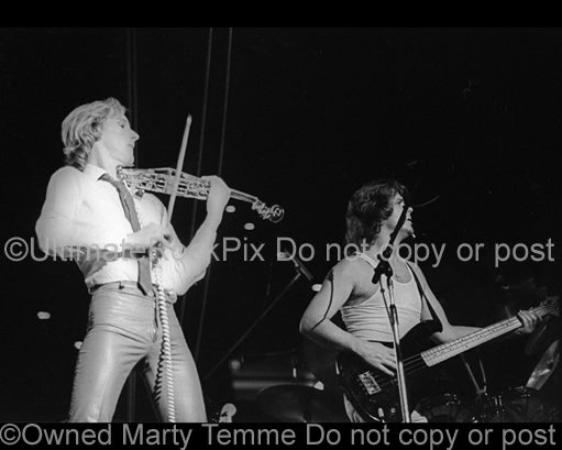 Photo of Eddie Jobson and John Wetton of the band U.K. in concert in 1979 by Marty Temme