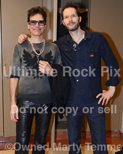 Photo of Steve Vai and Paul Gilbert standing together backstage after a concert in 2012 in Anaheim, California by Marty Temme