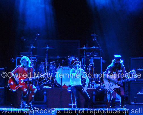 Photo of Scott Weiland, Duff Mckagan and Slash of Velvet Revolver in concert in 2008 by Marty Temme