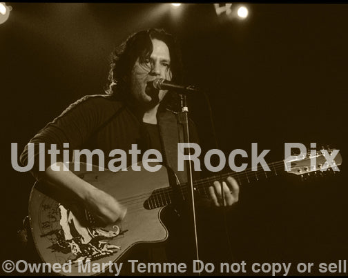 Black and white sepia tint photo of Kip Winger playing acoustic guitar in 2005 by Marty Temme