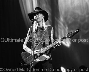 Black and white photo of Johnny Winter playing his Gibson Firebird in concert in 1998