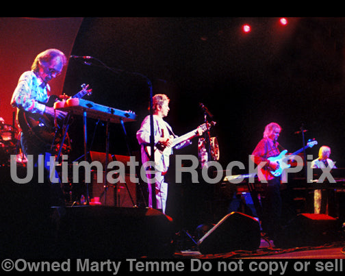 Photo of Steve Howe, Jon Anderson, Chris Squire and Rick Wakeman of Yes in concert in 2003 by Marty Temme