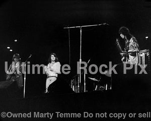 Photo of Steve Howe, Jon Anderson and Chris Squire of Yes in concert in the 1970's by Marty Temme