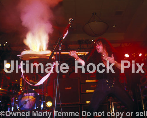 Photo of Yngwie Malmsteen with his guitar on fire in concert in 1994 by Marty Temme