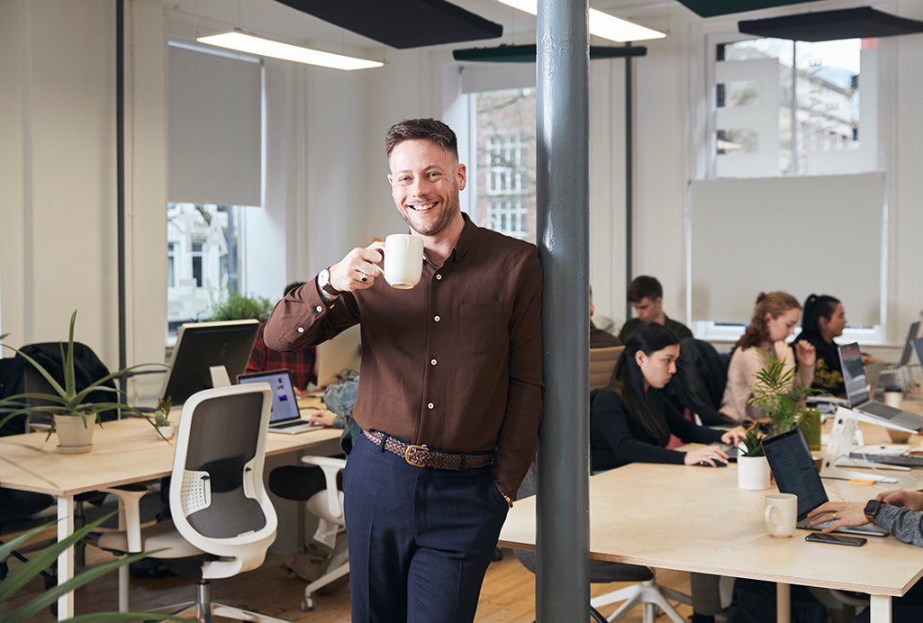 Lee leaning against a post in his office drinking a cup of coffee