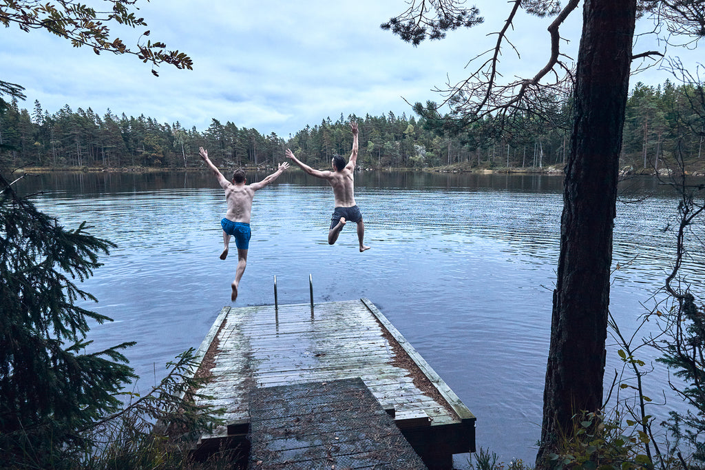 Rob and Chris jumping off a jetty into a lake