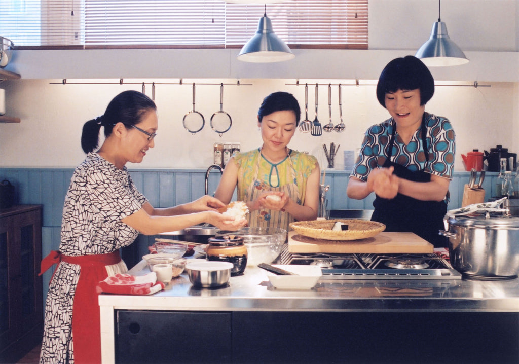 three japanese women making Omusubi (Onigiri, rice ball) in Kamome Diner - still from the film Kamome Shokudo