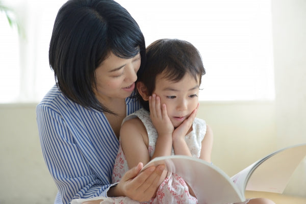 Image of a mother and a child. The mother is reading a book to the child at home.