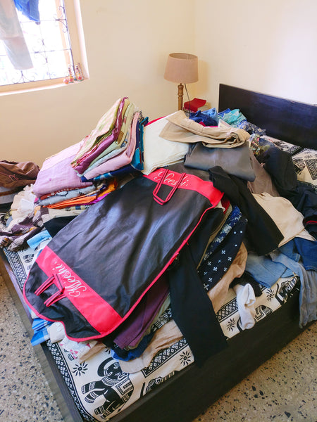 Almost all our clothes on the bed 1