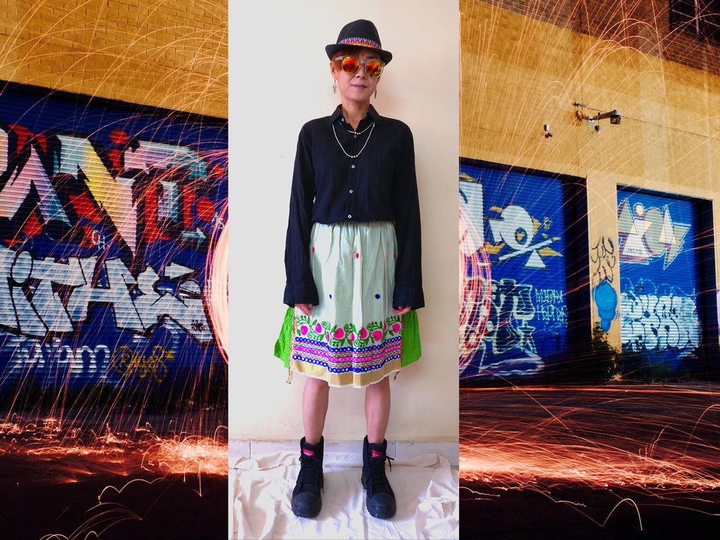image of a styling idea with knee-length cotton handloom tiered skirt with black shirt, black fedora hat, and black ankle sneaker
