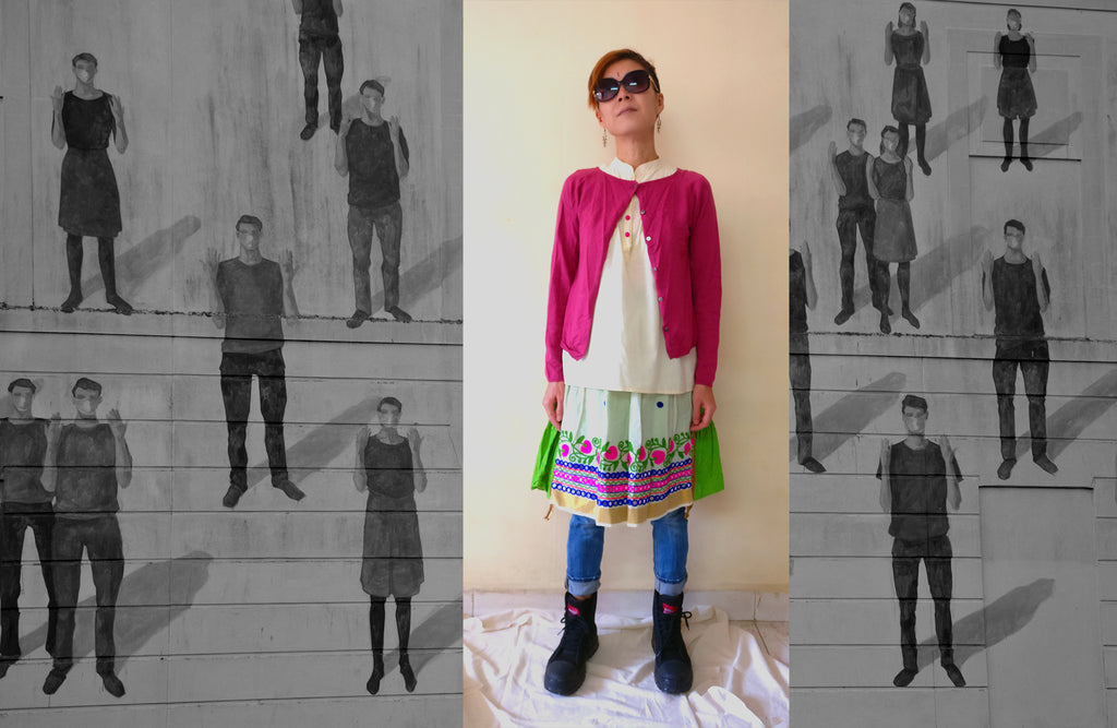 image of a styling idea with knee-length cotton handloom tiered skirt with pink woolen cardigan and skinny jeans