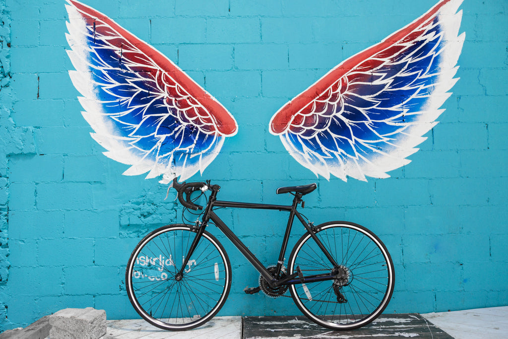 image of a bicycle near a wall with a painting of wings
