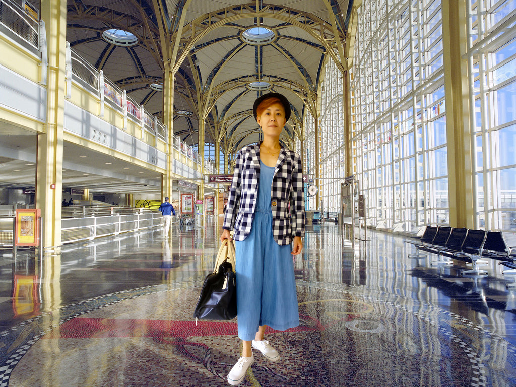 Image of an airport style outfit idea with a denim jumpsuit, cotton blazer jacket, and a hat