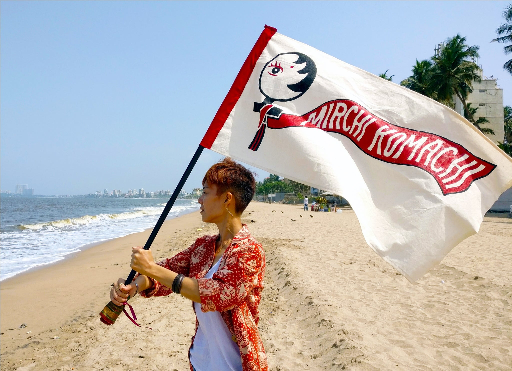 Image for About Us Page Yoshiko Inoue holding MIRCHI KOMACHI flag in the wind at Juhu Beach