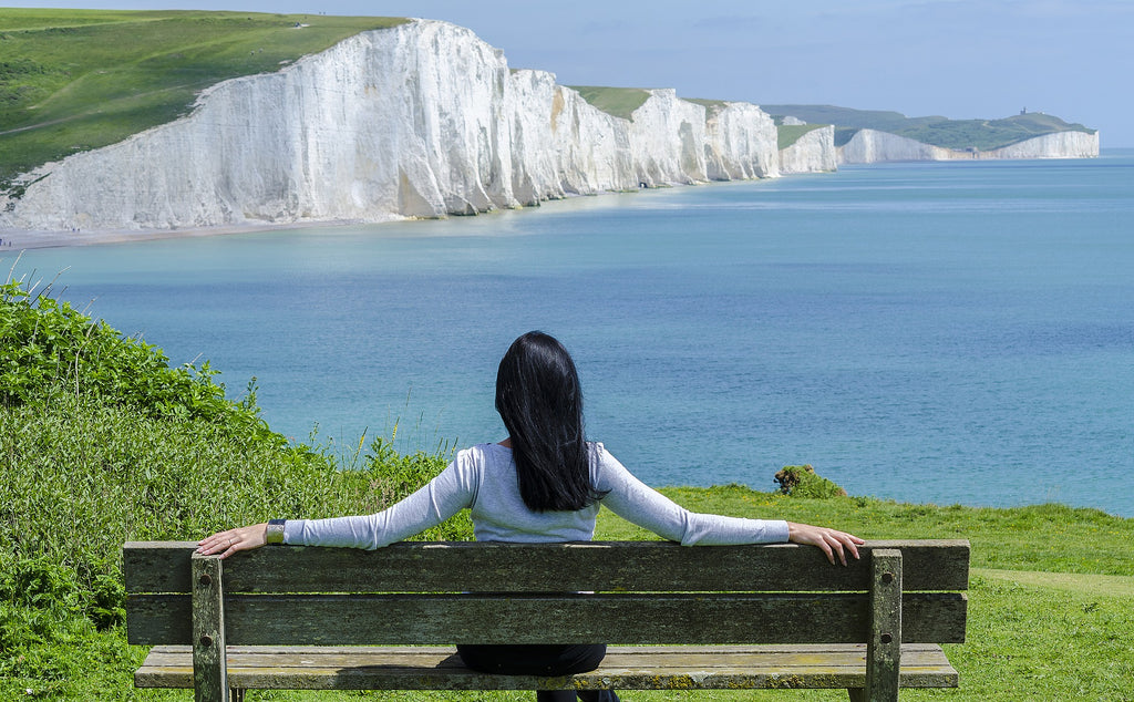 a woman sitting on a bench in front of a marvelous ocean view