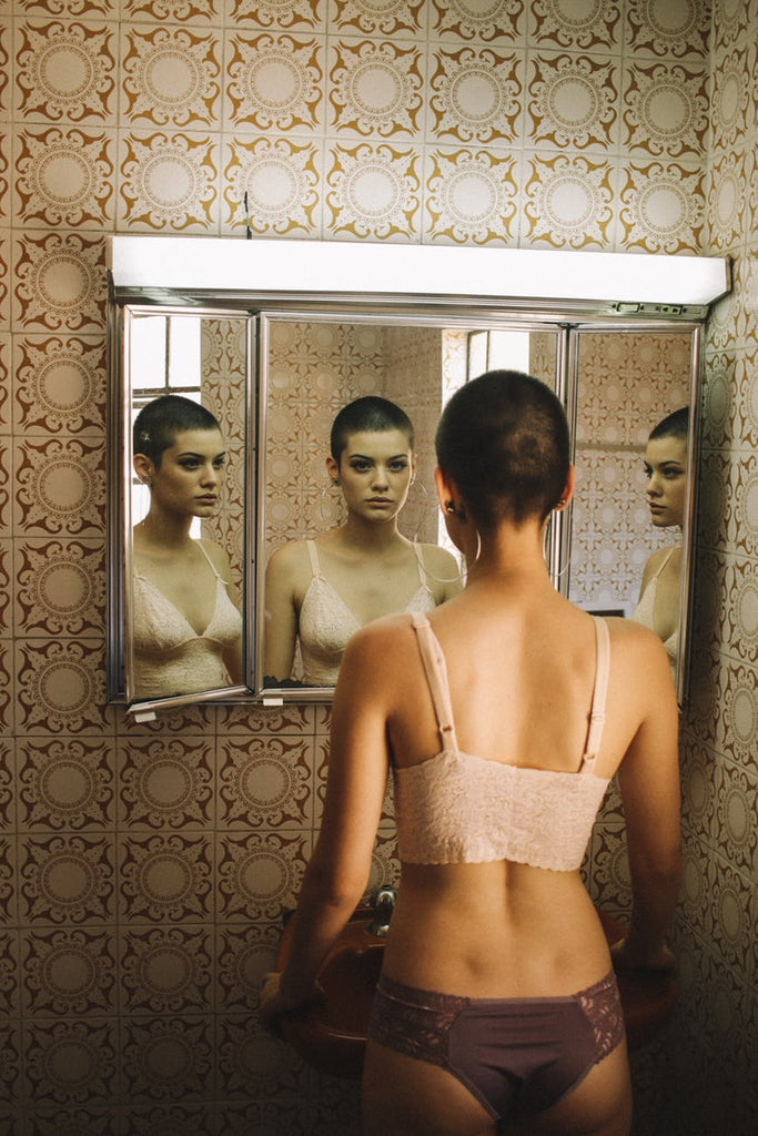 a woman with short hair standing in front of a mirror wearing underwear only