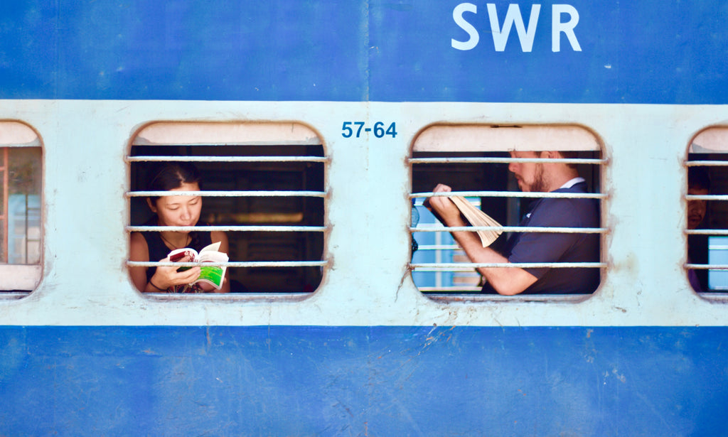 Image of a girl and a man reading books by the train window