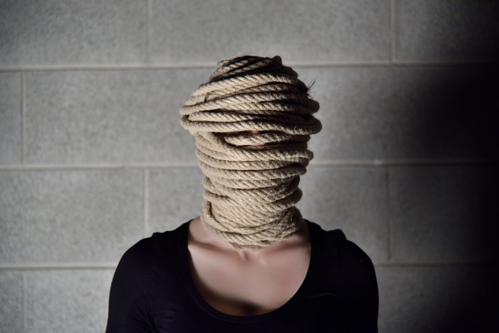 Image of a woman shut down by rope around her head and face