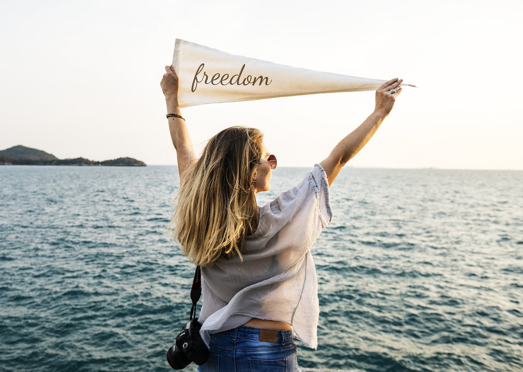 a woman by the ocean holding a flag saying freedom