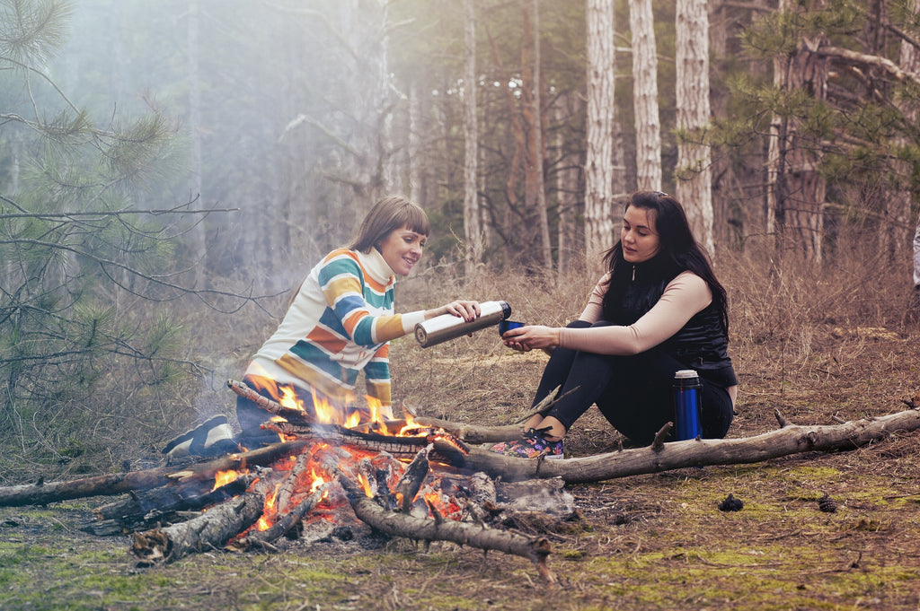 two women drinking by the fire in the forest