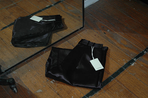 A pair of satin M.03 pants, folded and shot with its reflection in a nearby mirror. Shot in the Corepret studio on the ground, black pants contrast with the brown wooden floor boards
