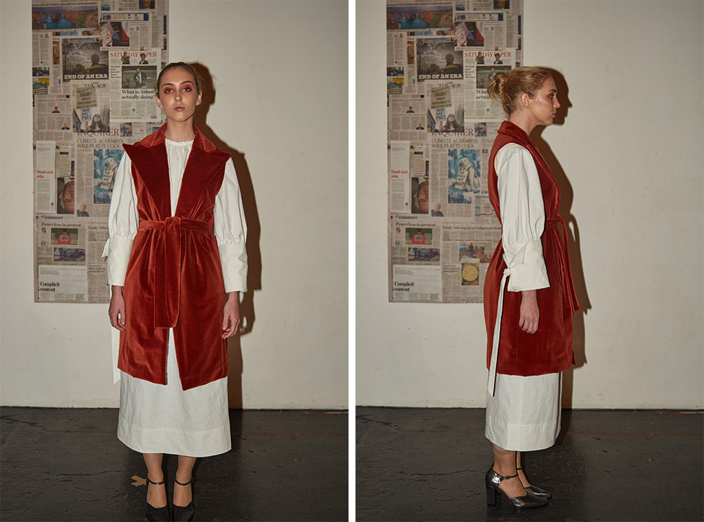 White cotton high-neck t-shirt dress with oversized sleeves paired with limited edition long red velvet waistcoat