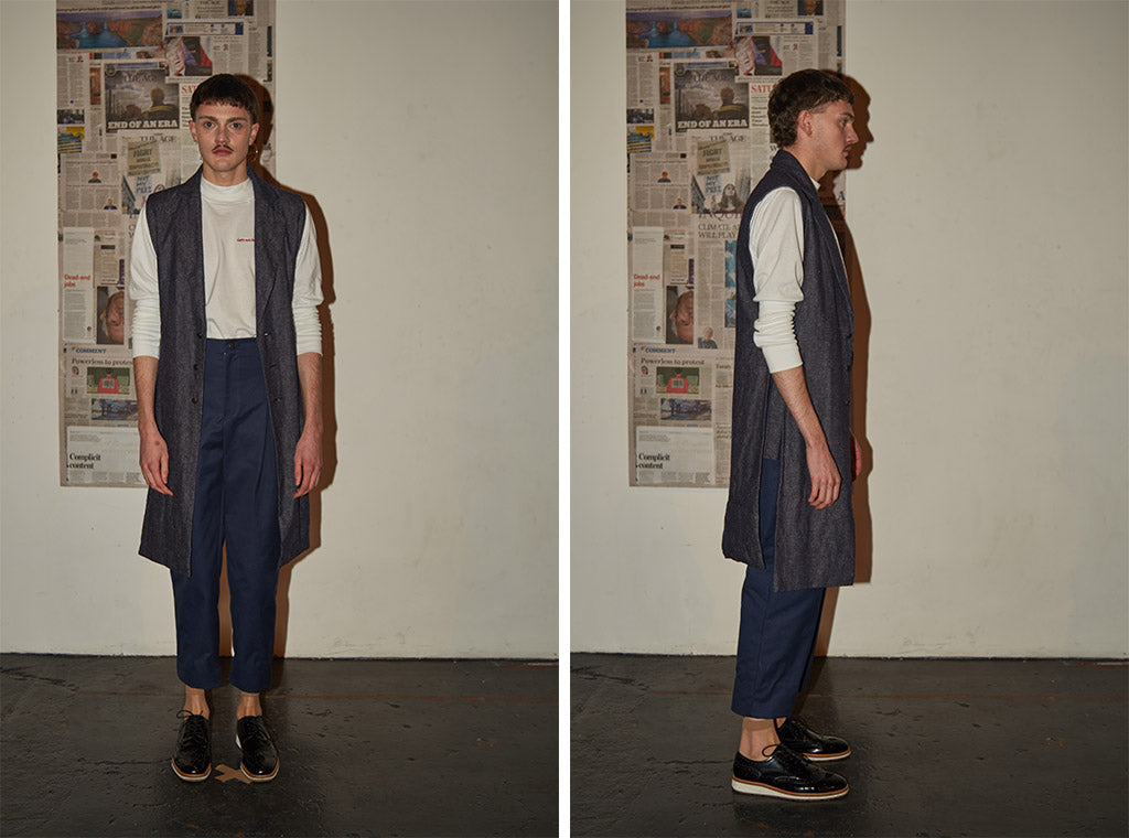 Tailored navy trousers paired with long-sleeve white cotton turtle neck top and sleeveless long denim waistcoat