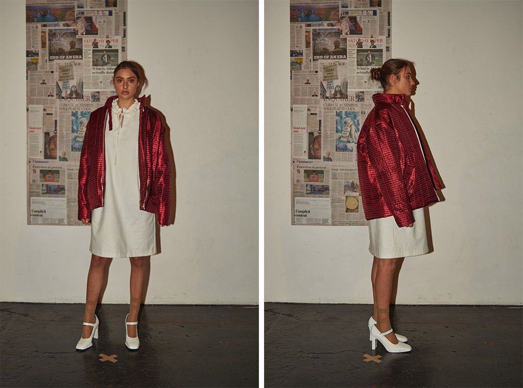 Mid-length dress with high ruffle neckline paired with limited edition metallic red bomber jacket