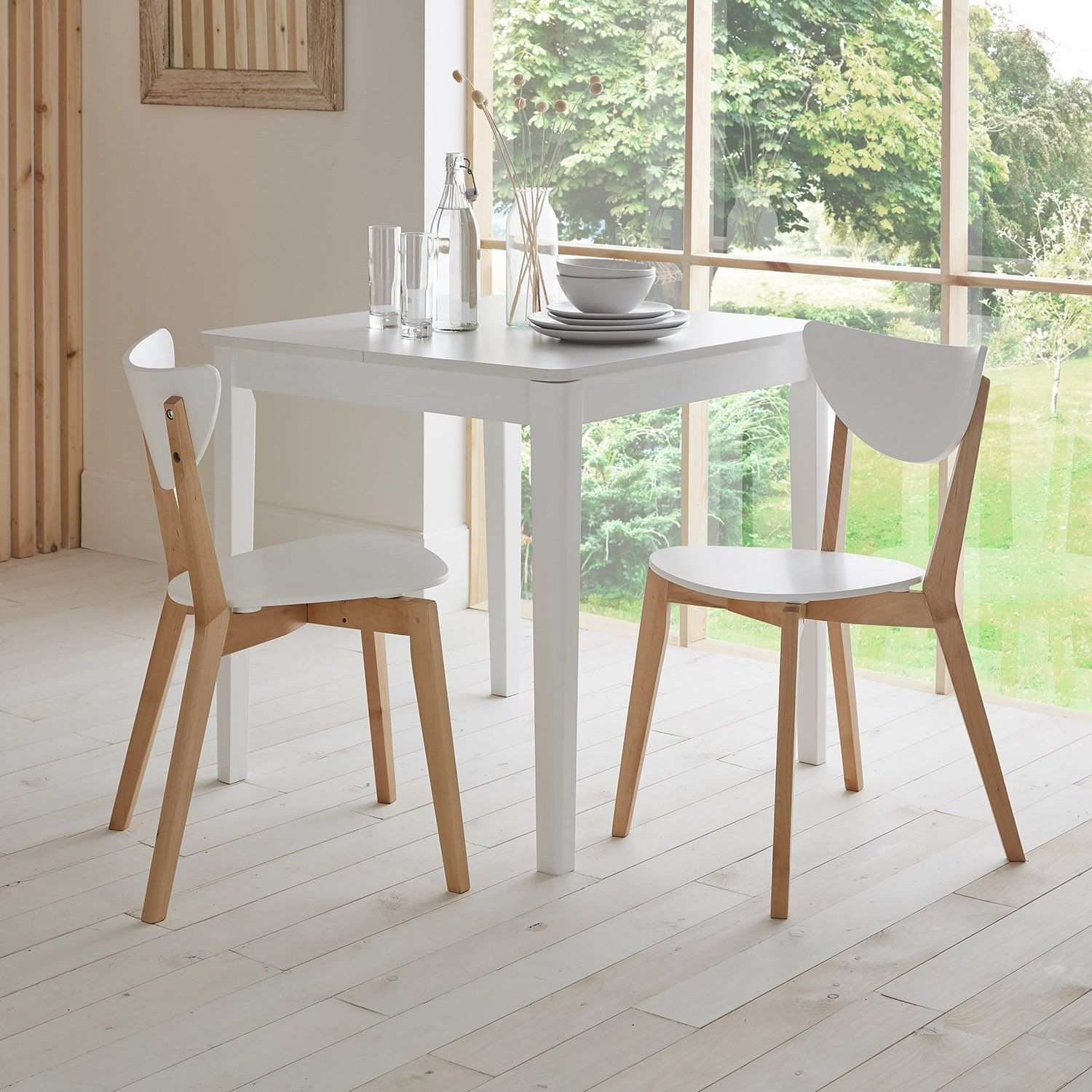 White extendable dining table with two chairs set beside a window