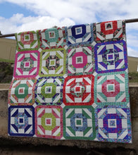 Churn it Round Paper Pattern.   Churn Dash Block variation. Uses Fat Quarters and a background fabric. Suitable for a confident Beginner quilter.