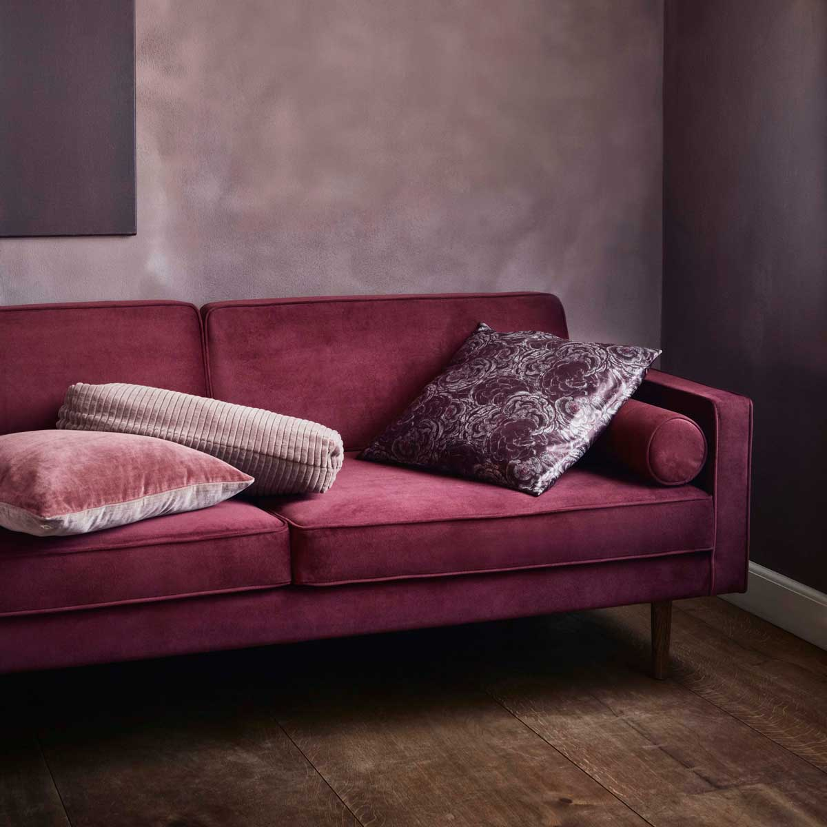 red wine coloured sofa with purple and pink cushions from broste copenhagen