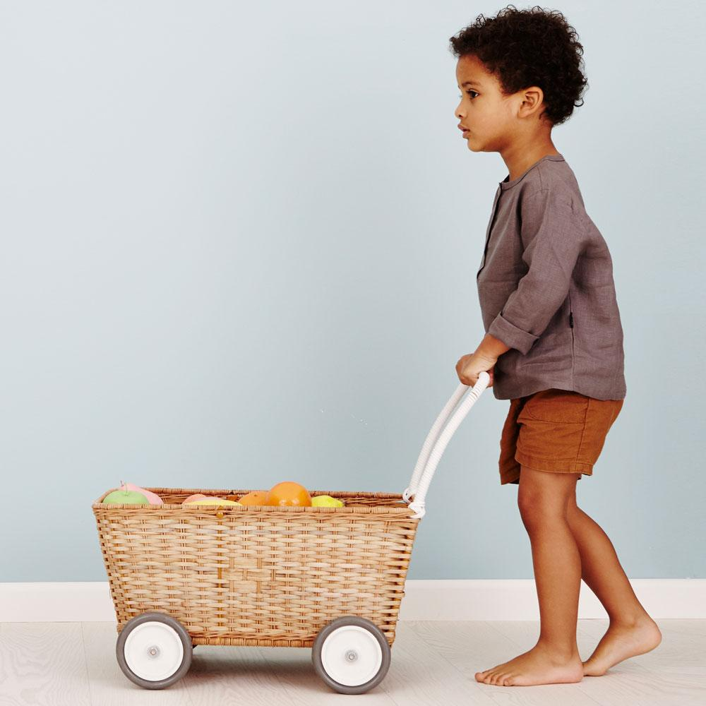 wicker basket shopping cart with wheels and a handle with boy pushing