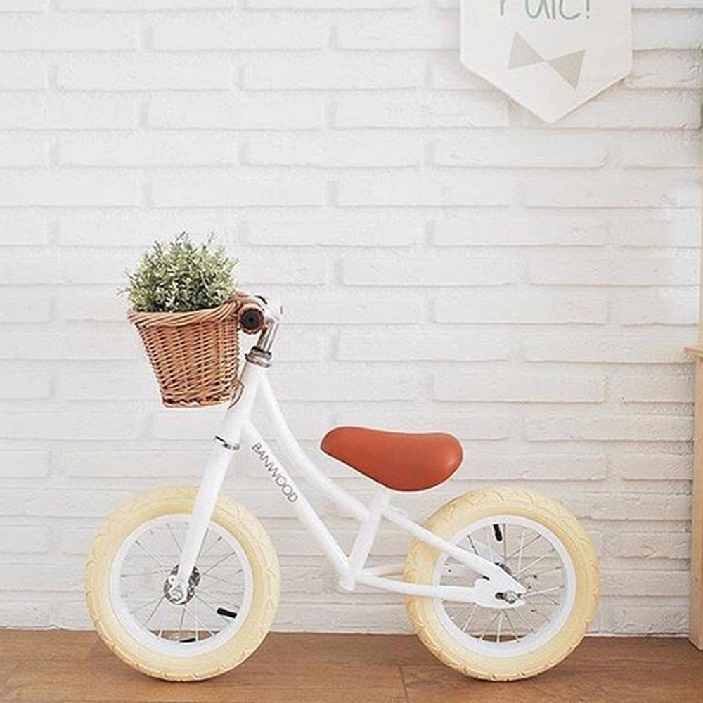 White Banwood first go balance bike with basket of flowers