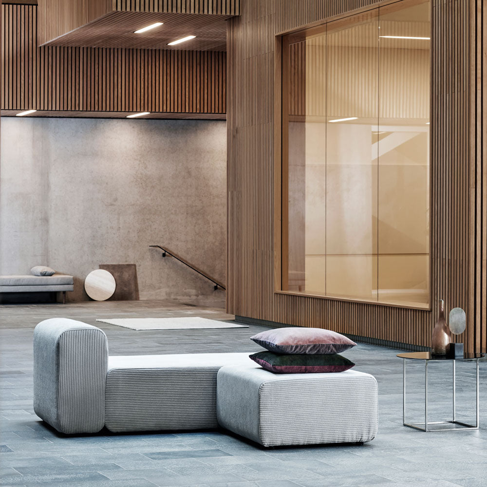 Modular sofa in Corduroy fabric by Broste Copenhagen photographed in a beautiful huge room with wood clad walls