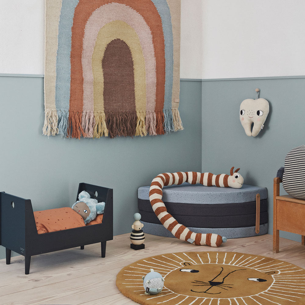 childrens playroom with rainbow wall hanging and lion rug