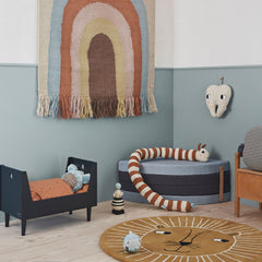 oyoy living design mini collection with lion rug, rainbow wall hanging, brown and white snake toy cot and tooth fairy on the wall.