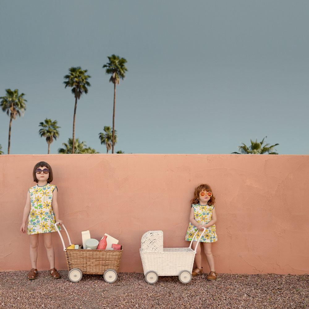 two girls against pink wall with blue sky and palm trees with Olli Ella Prams and strolleys