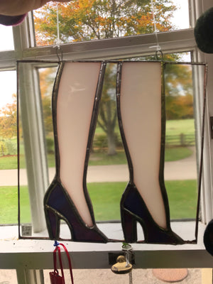 Ladies legs in high heels. Stained glass.