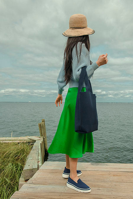 Woman wearing our Navy Knit Sneaker and Navy Sutton Tote Bag on a pier by the ocean