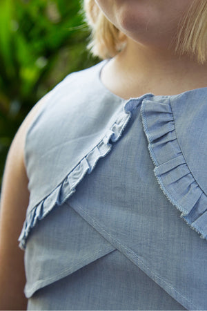 Close up of girls plus size chambray dress with ruffled top while Ruthie is wearing