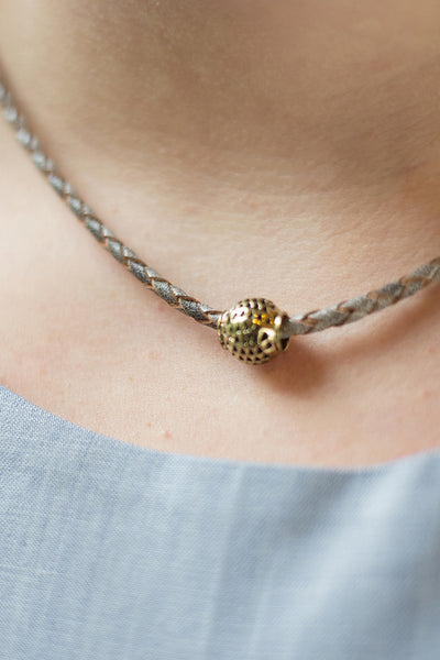 Ruthie wearing the gray leader choker with brass bead charm