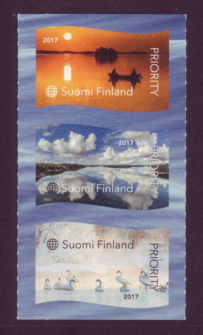 Three stamps from Finland 2017 showing  small boat on a lake, clouds in the sky and swans.