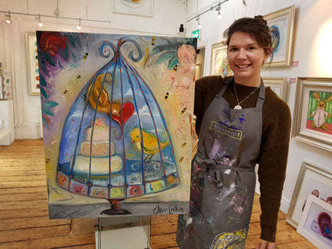 Dawn Crothers holding one of her completed oil paintings