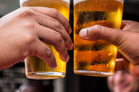 Two hands holding full beer glasses and toasting with their glasses