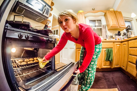 blonde woman wearing christmas pajamas pulling cookies out of an oven
