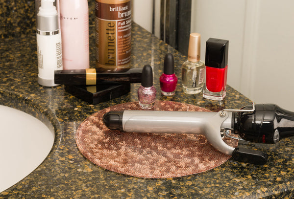 Doing makeup and hair with a silicone trivet to protect counter top from curling iron