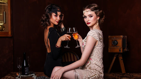 Two women toasting with their champagne glasses, dressed in 1930s hollywood party dresses