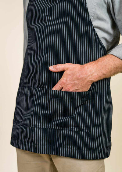 Closeup of black apron with pockets, with a hand in one pocket.