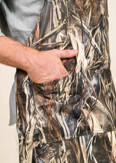 A closeup of a hand in the pocket of a camo apron